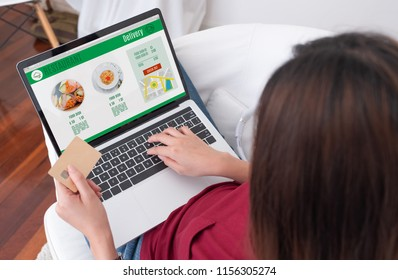 Close up woman sitting use credit card pay for food online order on laptop computer in add to cart function webpage at home,Digital marketing concept.digital lifestyle living