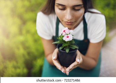 Close up of woman smelling a flower while working as a gardener in a large online store. Enjoying work at its best. Unemployment never been so close.