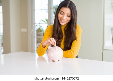 Close up of woman smiling putting a coin inside piggy bank as investment