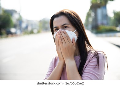 Close up of a woman in a suit wearing Protective face mask and cough, get ready for Coronavirus and pm 2.5 fighting against beside road in background.