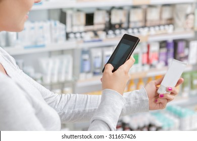 Close up of a woman taking picture of the product in drugstore