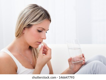Close up of a woman taking pills holding glass of water