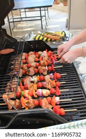 Close up of a woman turning kebabs for the BBQ symbolising Summer, barbecues, healthy lifestyle and al fresco dining