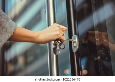 Close up of woman unlocking entrance door with a key. Person using key and locking apartment door.