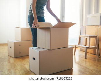 Close up of woman unpacking cardboard box in new home. Moving into new home. Moving house and cardboard boxes