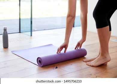 Close Up Of Woman Unrolling Yoga Mat Before Exercise