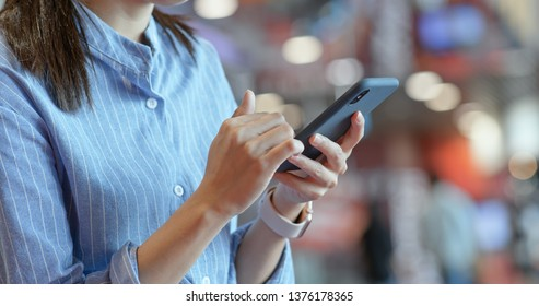 Close up of woman use of mobile phone inside shopping center