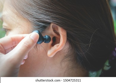 Close up of woman is using the black true wireless earbuds by hand to put in ear and control