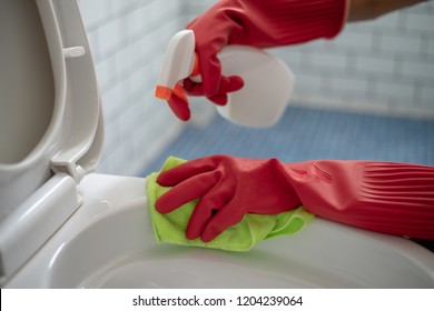 Close up woman using cleaning spray clean a toilet.