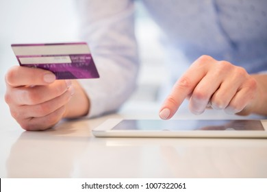 Close Up Of Woman Using Credit Card To Make Purchase On Digital Tablet