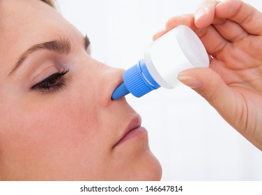 Close up of a Woman using nasal spray isolated on white background