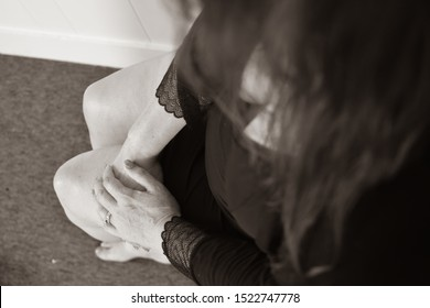 close up of a woman view over the shoulder wearing black nightgown and robe with brunette hair hands on knees