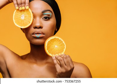 Close up of woman with vivid makeup and orange slices in hand. Female model with copy space over yellow background.