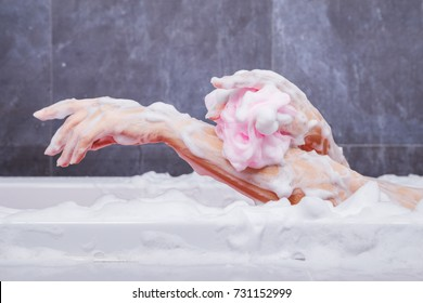 close up of woman washing arm with pink sponge in bathtub in the bathroom