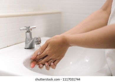 Close up woman is washing her hand under running water in bathroom. Hygiene. Cleaning hands at washbasin.