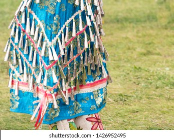 Close up of a woman wearing a blue brocade jingle bead dress and beaded leggings photographed at a pow wow in Montana.