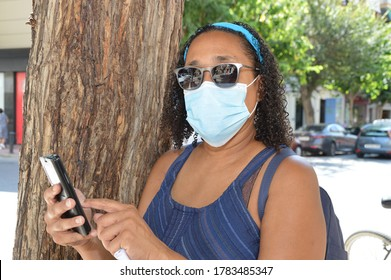 Close up of woman wearing face mask leaning on tree during pandemic