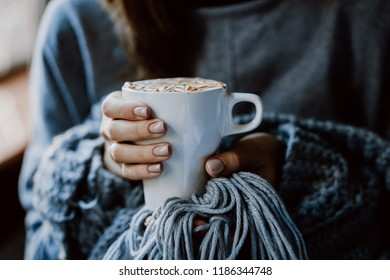 Close up of a woman wearing grey sweater and scarf with hands holding a drink cup beside a window in coffee shop