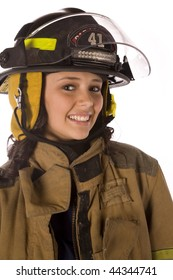 A close up of a woman wearing her fire fighters helmet with a smile on her face.