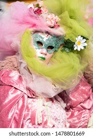 Close up of a woman wearing a typical Venetian carnival mask wrapped in bright veils of pink and green colors with floral motifs on the head