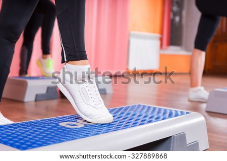 Close Up of Woman Wearing White Sneakers Doing Toe Tap on Step Platform in Aerobic Exercise Class with Group of Women in Background in Dance Studio
