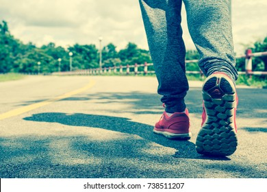 Close Up of Woman Wears Sneaker Shoes Walking on The Road. Vintage Style. Copy Space for Text.