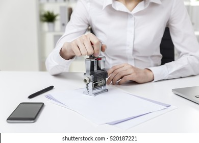 Close up of a woman in white blouse who is sitting in the office and stamping a treaty. Concept of notary work