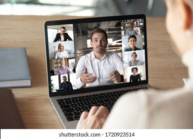 Close up of woman worker talk brainstorm on video call on computer with diverse colleagues, have online team briefing together, female employee engaged in webcam conference on laptop with coworkers