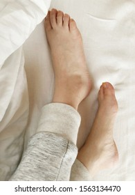 Close Up Of Woman's Barefoot On Bed.