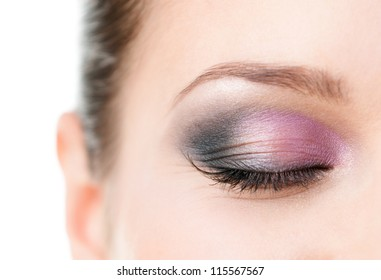 Close up of woman's closed eye with makeup of pink and grey eye shades, isolated on white