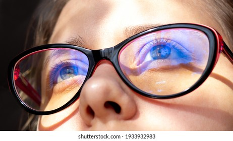 Close up of woman's eyes with red and black female glasses for working at a computer with a blue filter lenses. Anti blue light and rays. Eye protection