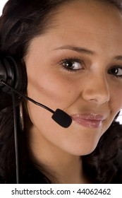 A close up of a woman's face with a headset with a small smile on her face.