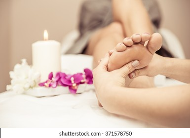 Close up of woman's feet and beauty saloon decorations. Beautician making foot massage. Concept about body care, spa and massages