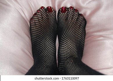 Close Up of Woman's Feet in Black Fishnet Stockings with Shiny Red Polish on Pretty Toenails Beautiful Pedicure on Soft Pink Silk Shiny Bedding - Classic Fishnet Tights