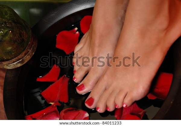 Close up of a woman's feet on a rose pedal bath,