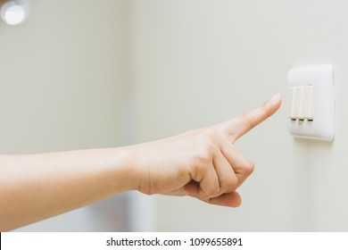 Close up of woman's finger is turning on or off on light switch