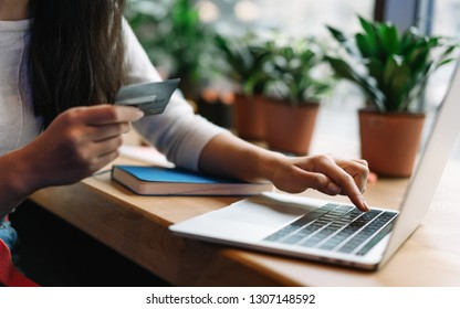 Close up woman's hand holding credit card using laptop computer for online shopping with cash back, discount sales, low prices. Online store concept. Female planning travel and booking tickets.