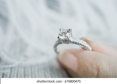 Close up of woman's  hand holding elegant diamond ring with feather and gray Scarf background. Diamond ring.