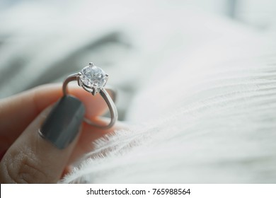 Close up of woman's hand holding elegant engagement diamond ring with white feather background. Love and wedding concept.