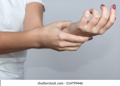 Close up woman's hand holding her wrist  over gray background