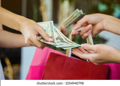 close up of a woman's hand holding shopping bags and paying  cash money dollars . People, Shopping, Sale and Consumerism concept