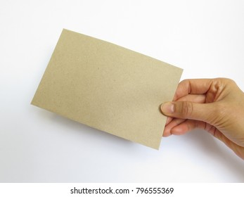 Close up of woman's hand holds a brown envelope  on white background
