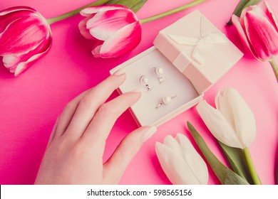 Close up of woman's hand with jewellery and tulips