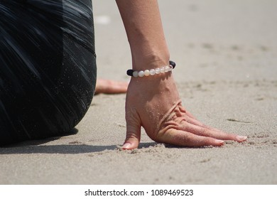 Close up of womans hand on beach