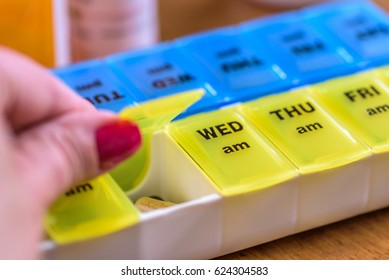 Close up of a woman's hand opening a pill holder for daily medications
