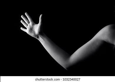 Close up of woman's hand and part of a shoulder isolated on black background.