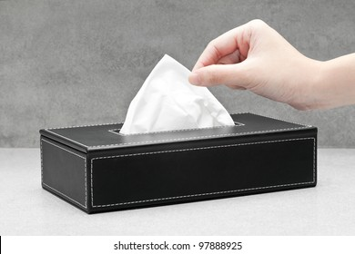 Close up of a woman's hand pulling a facial tissue from a black tissue box
