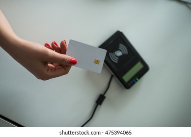 Close up of woman's hand putting a credit card on a machine