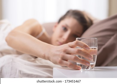 Close up of woman's hand taking a glass of water