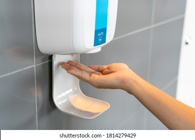 Close up of woman's hand using alcohol gel disinfecting hands. Cleaning, washing hands using automatic sanitizer dispenser concept.